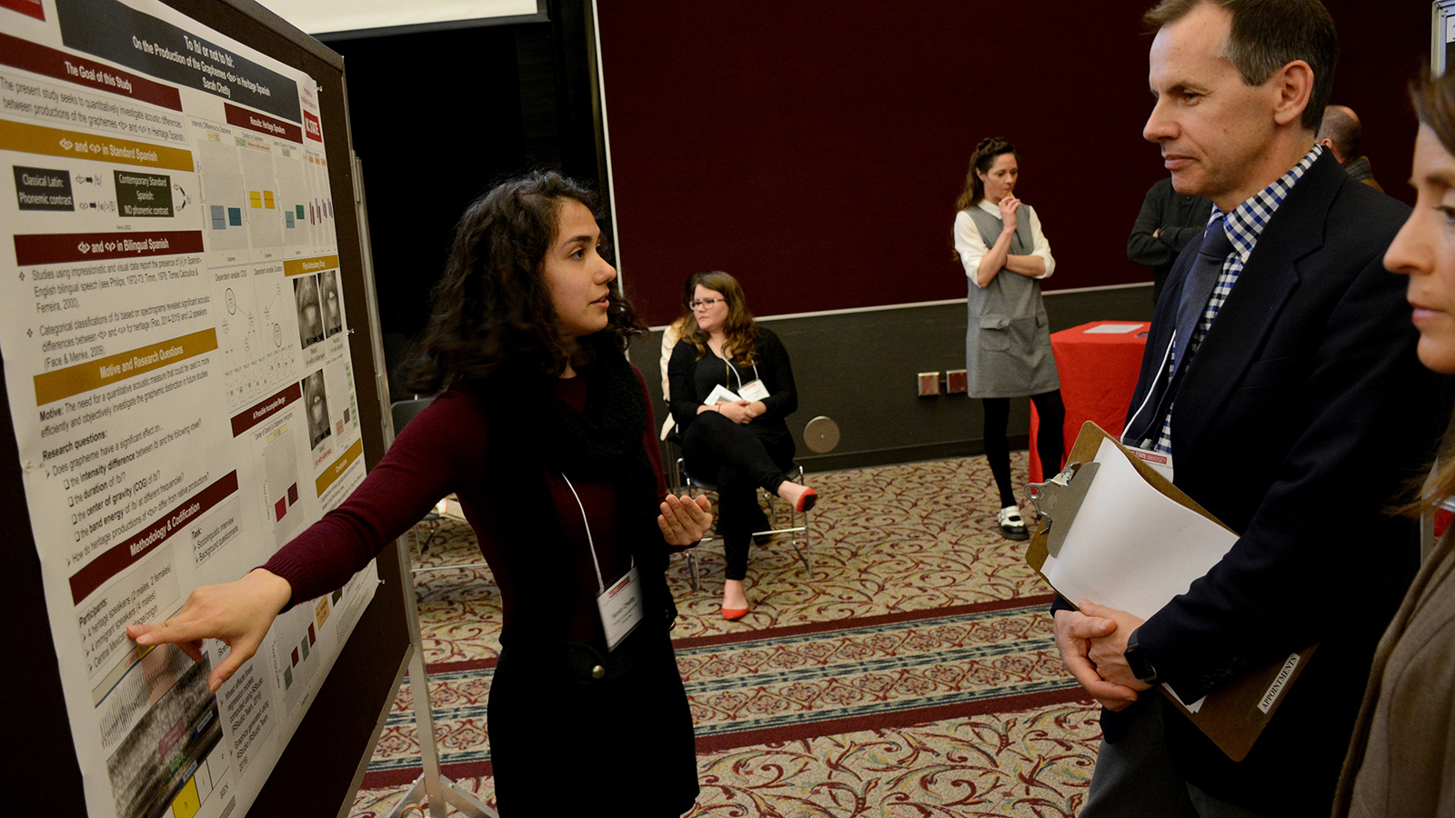 A student points to their poster while talking with two faculty members.