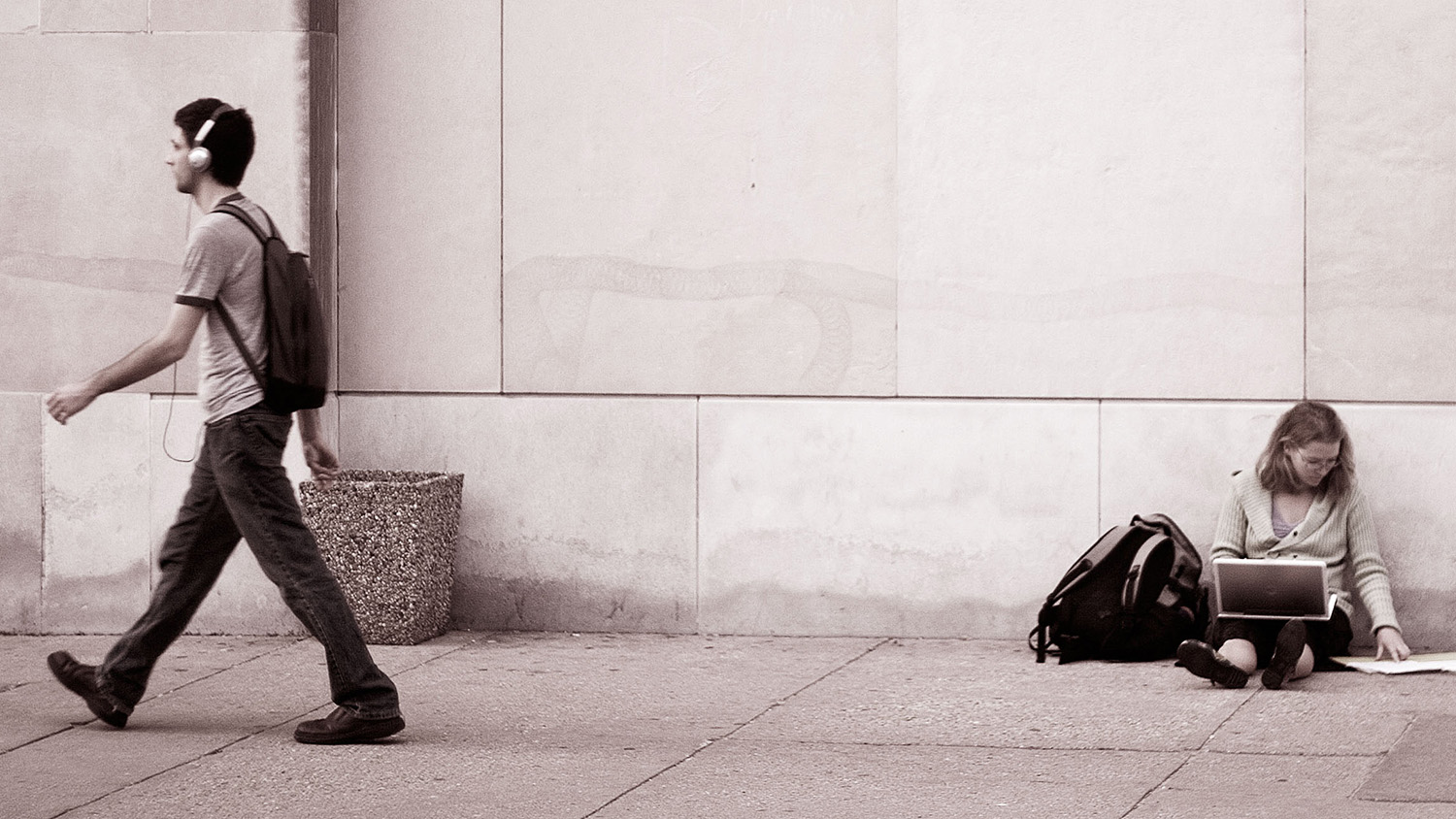 Man walks on the sidewalk with headphones. Woman sits on the ground.