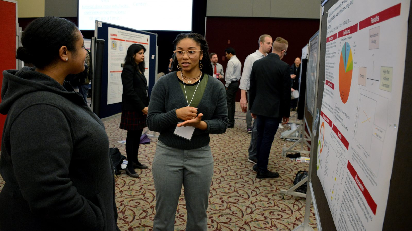 Kristen Pender stands near her research poster and talks with Elan Hope.