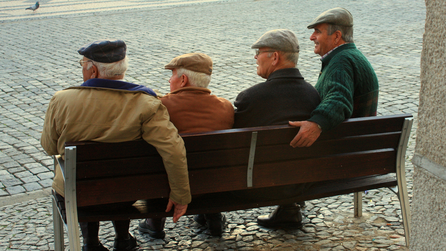 Four men sit on a bench.