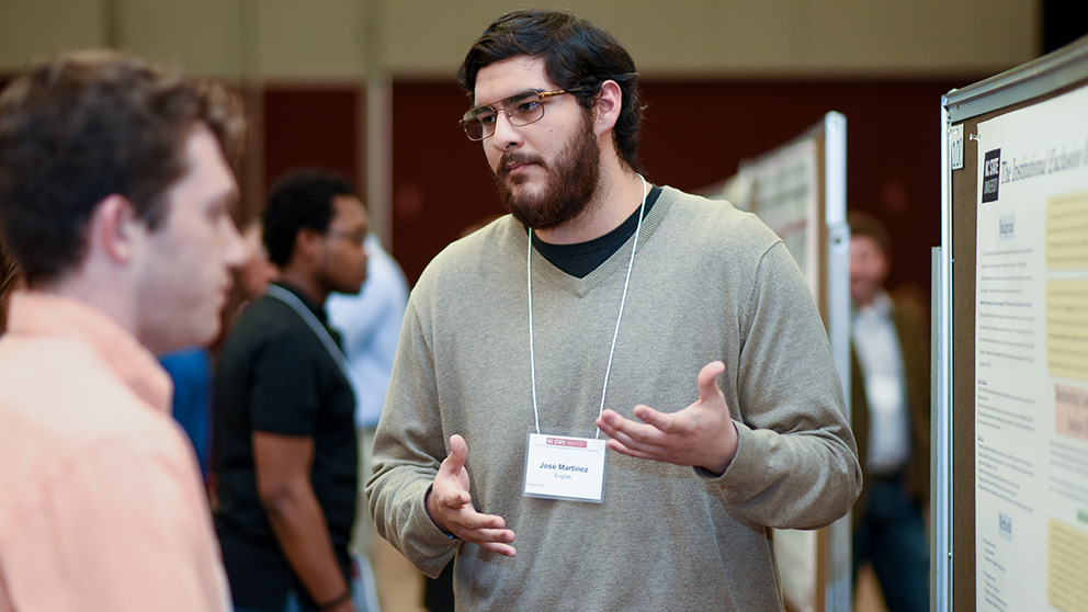 Jose Martinez talks to a visitor at the NC State Graduate Student Research Symposium