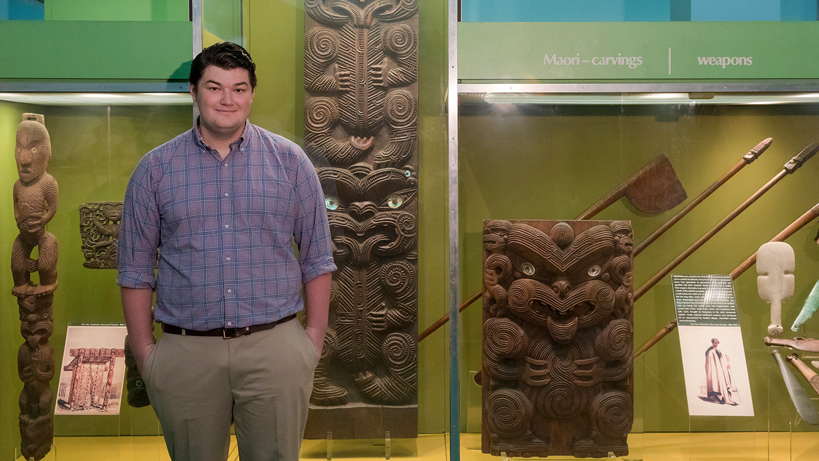 Colin Gravelle stands in front of a case of Maori artifacts.