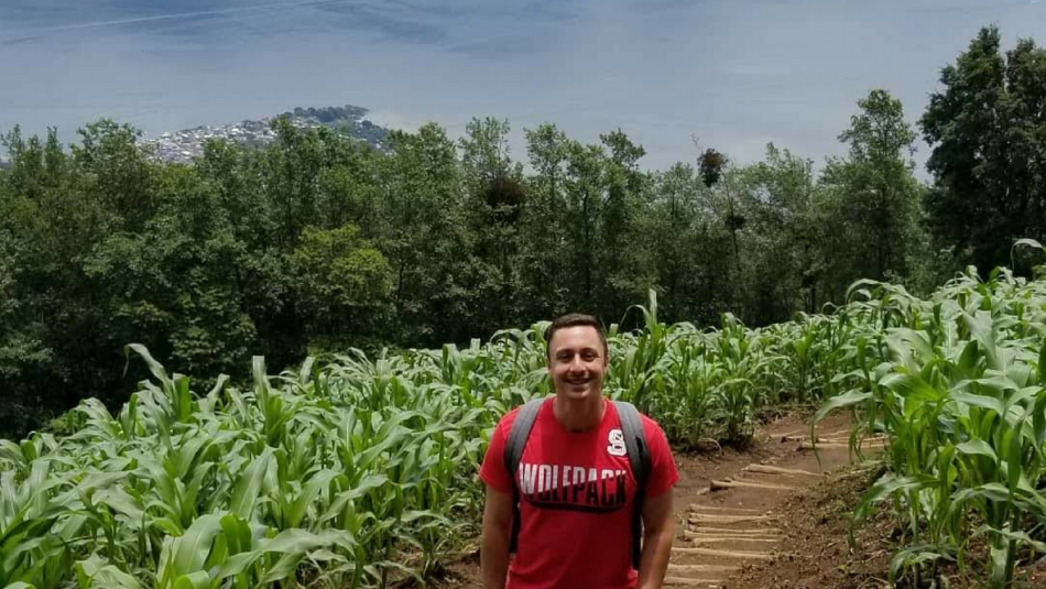Douglas Mulford stands in a field of crops at Lake Atitlan in Guatemala