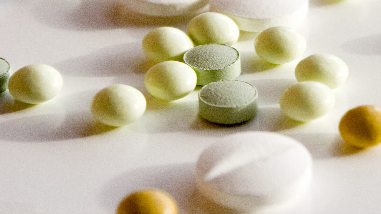 An assortment of pills sit on a white table