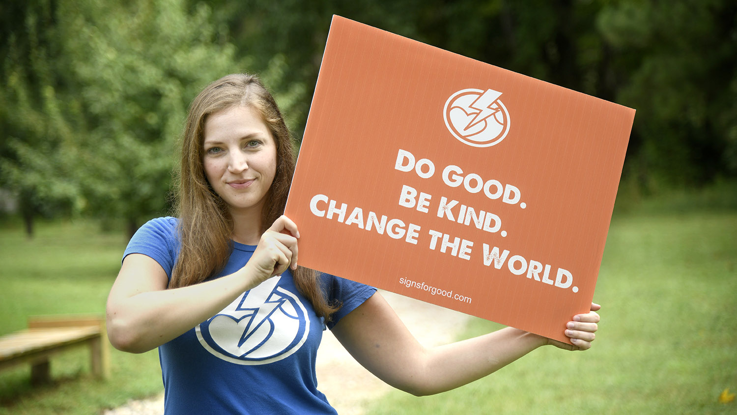 "Wearing a blue Activate Good T-shirt, Amber Smith holds up an orange sign that reads, ""Do Good. Be Kind. Change the World."""