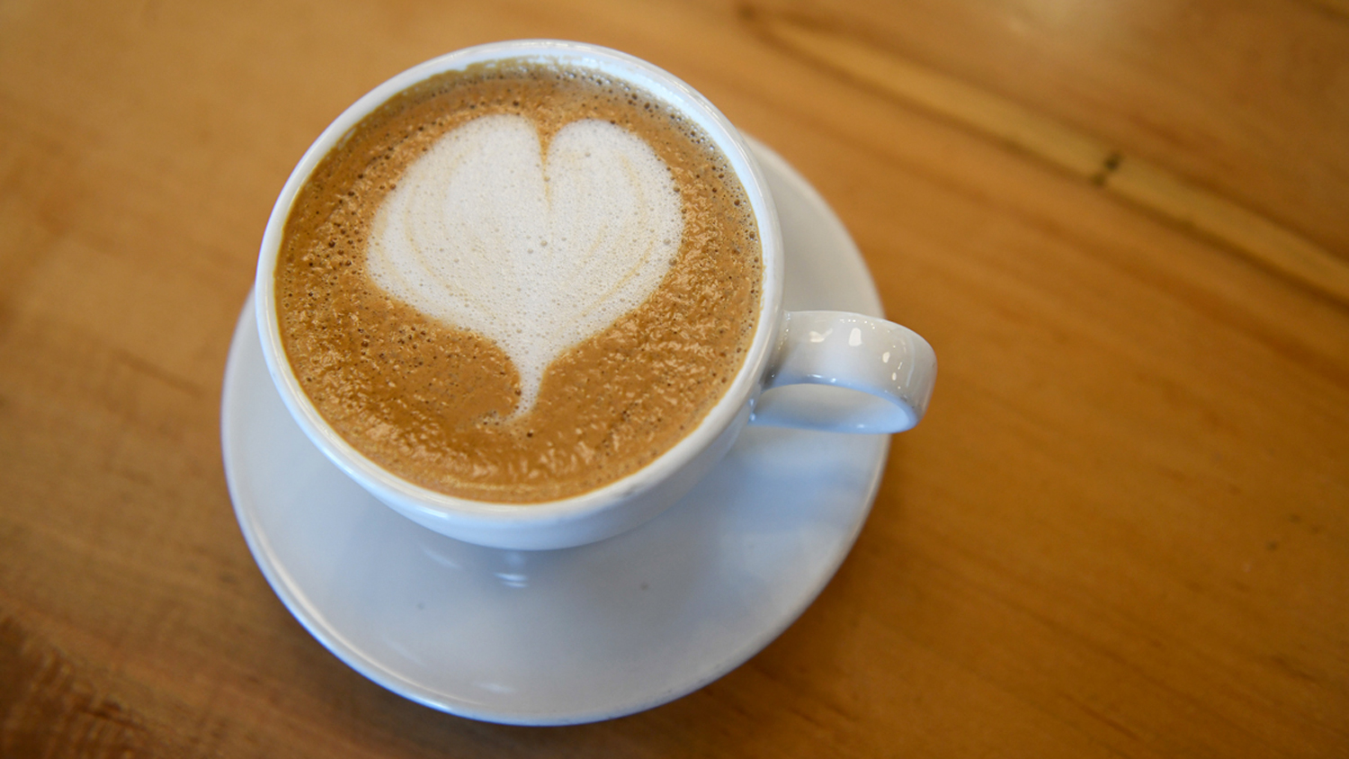 A heart shape appears in a cup of coffee