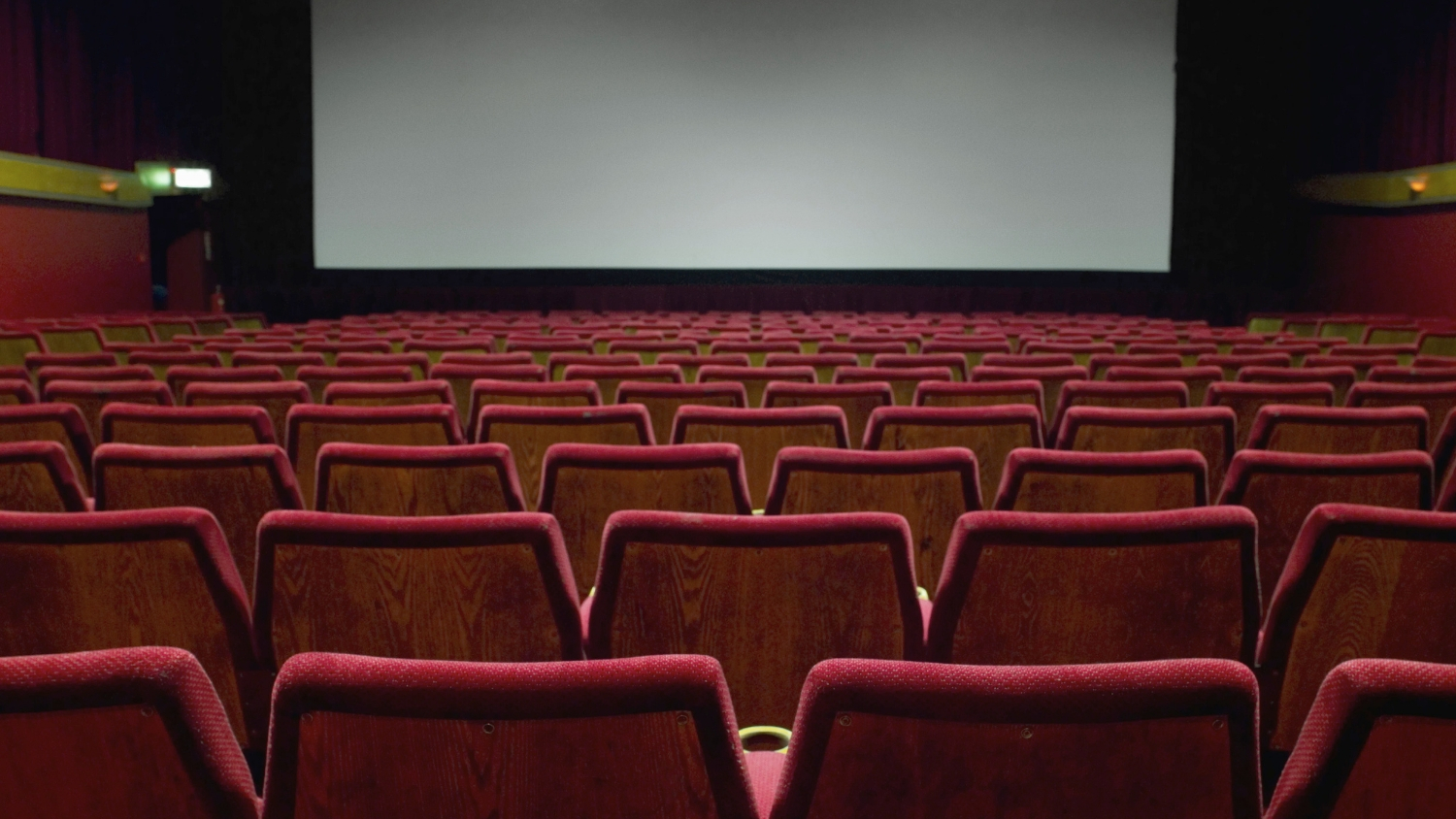 rows of red chairs in an empty movie theater