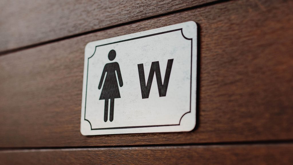 "A restroom sign shows a silhouette of a woman and the letter, ""W""."