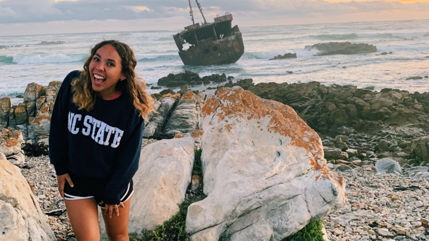 student standing on beach with ship in background