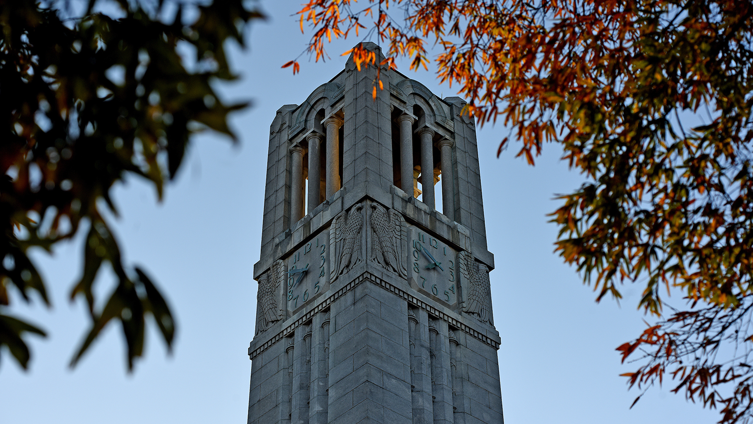 belltower peaks out of changing fall leaves
