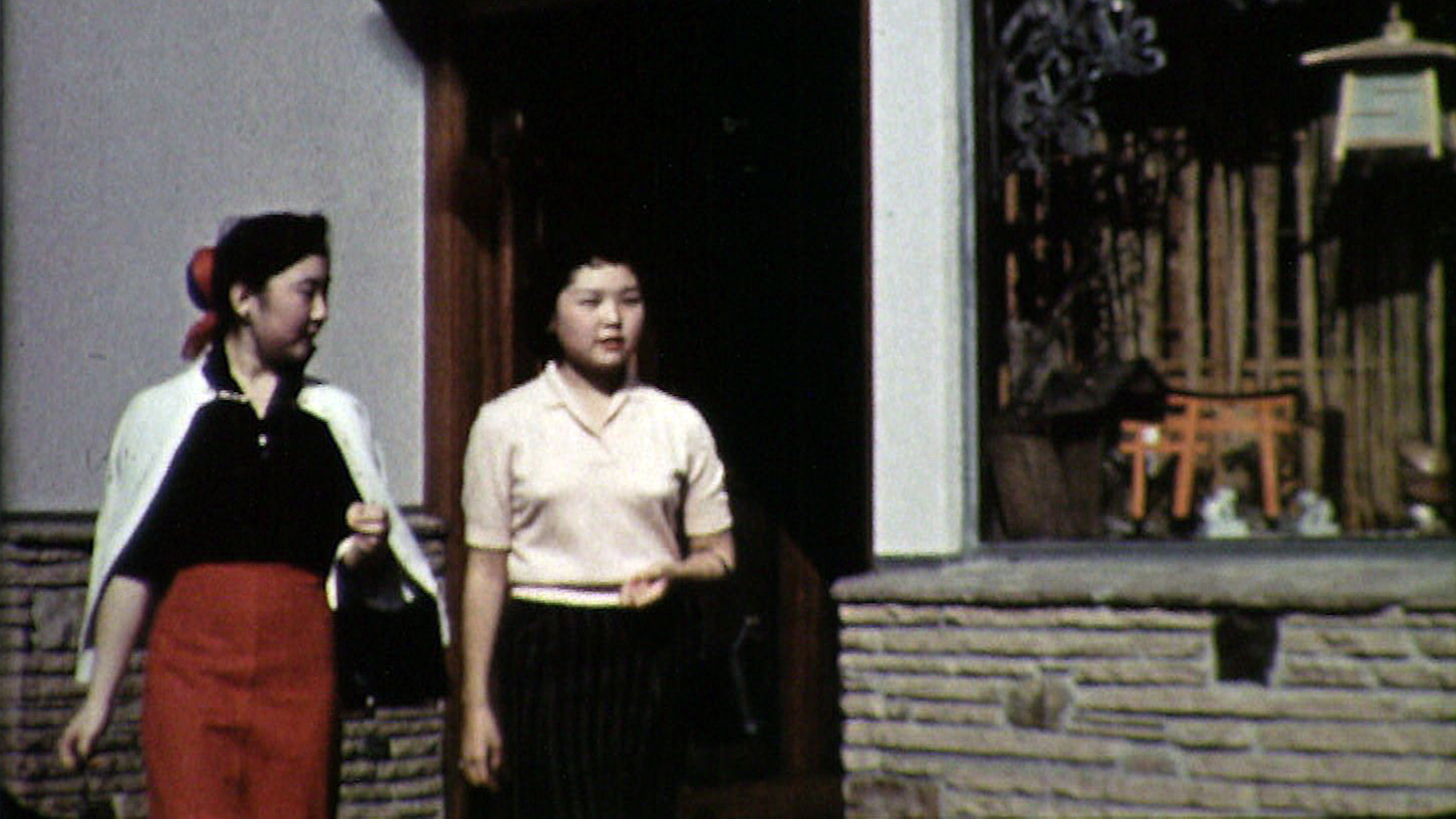 two asian-american girls walk down the street