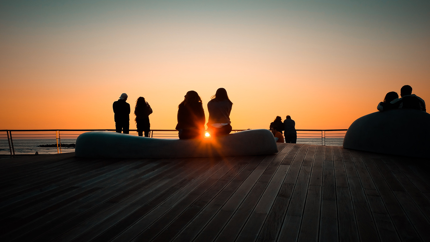 couples in silhouette in front of a sunset