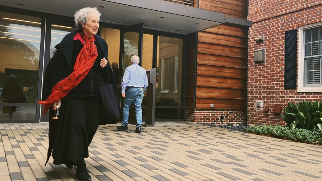 Margaret Atwood walking out of museum dressed in black with red scarf