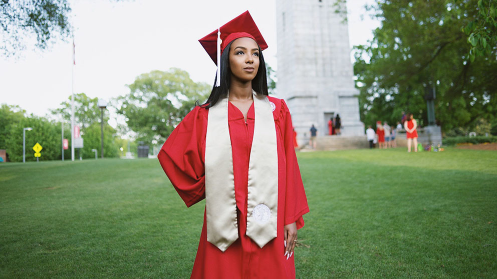 A student stands in her cap and gown in front of the NC State belltower.