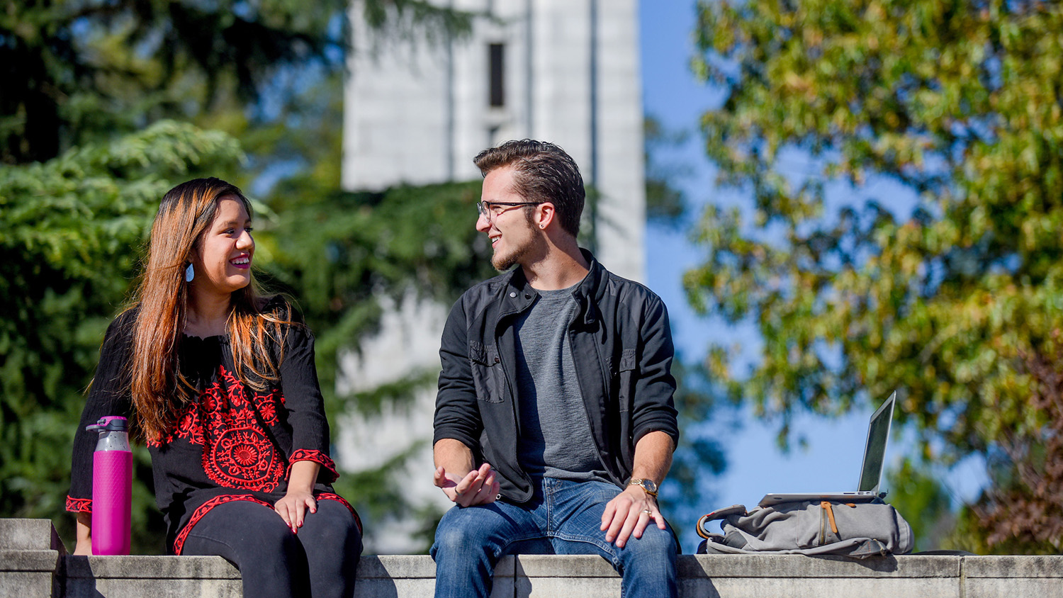 two students sitting on ledge in front of belltower