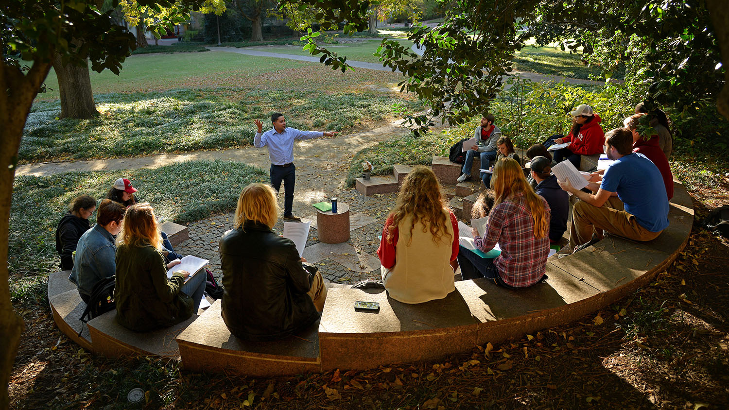 A faculty member addresses students in an outdoor classroom