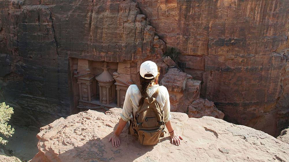 A student looks out over a ridge in Petra, Jordan.
