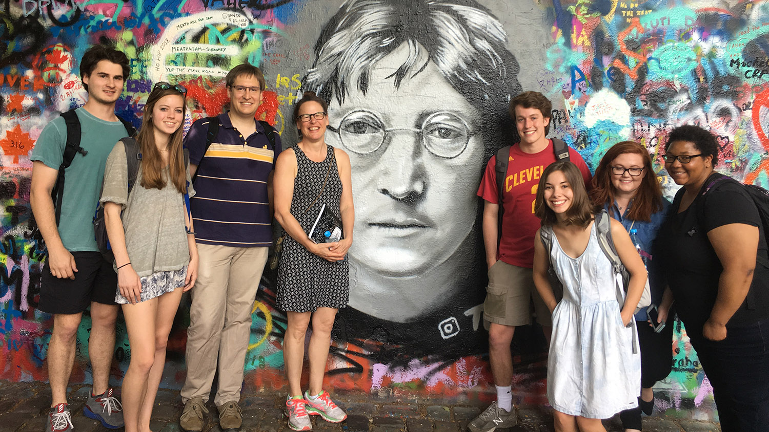Students pose next to a mural of John Lennon while studying abroad in Prague