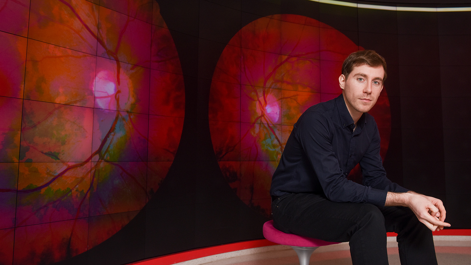 Tim Prudhomme sits in front a screen that displays retina images.