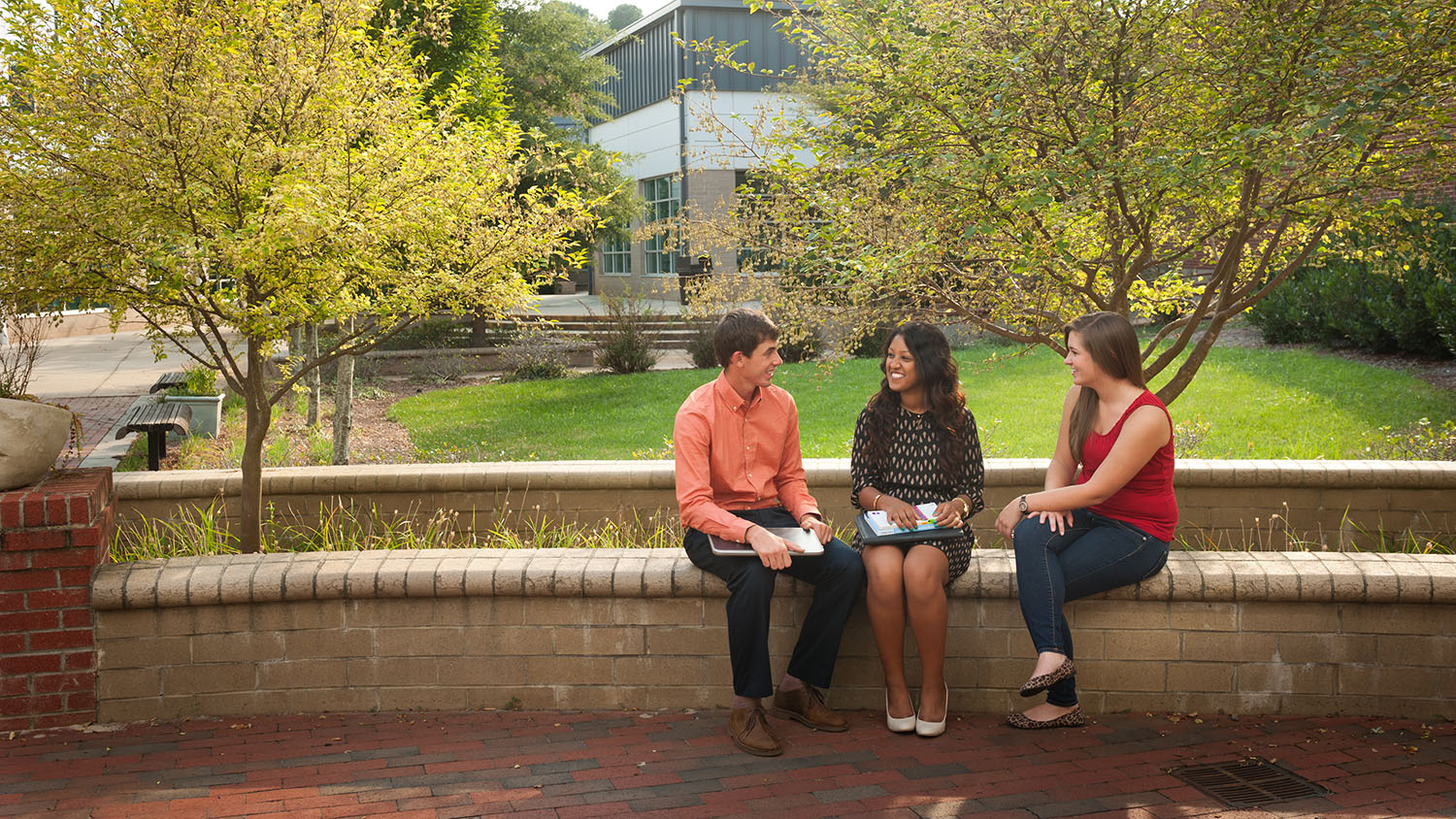 three students sitting on brick ledge