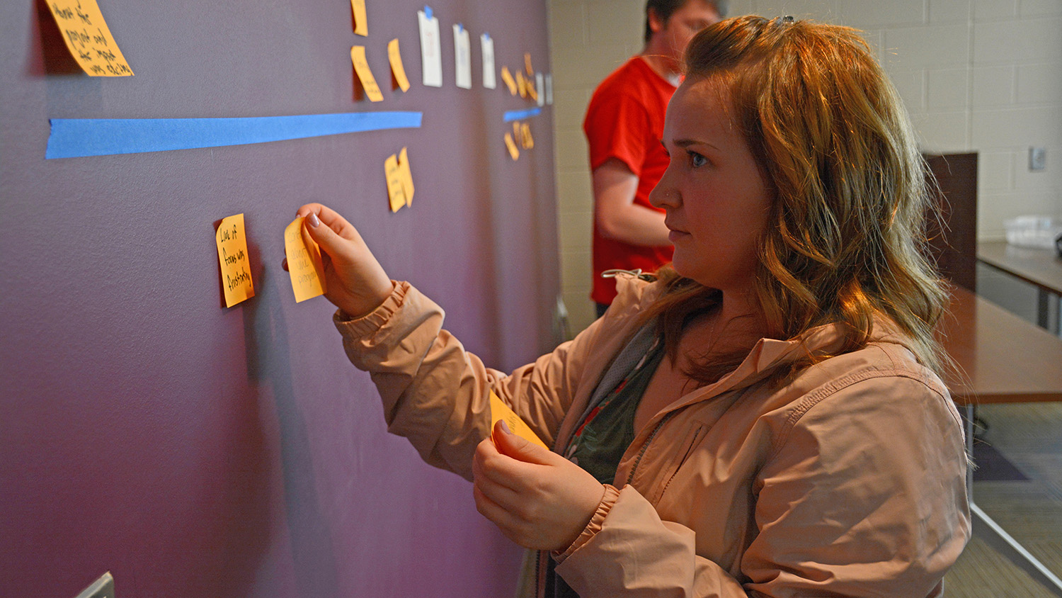 A student places a stickey note on a wall