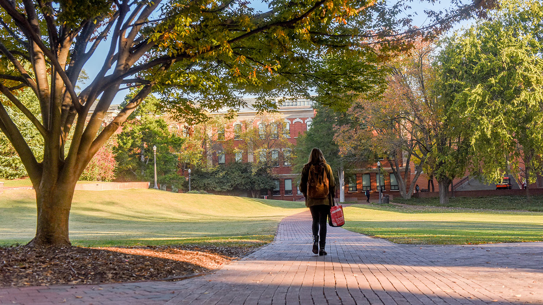student walks on brick path