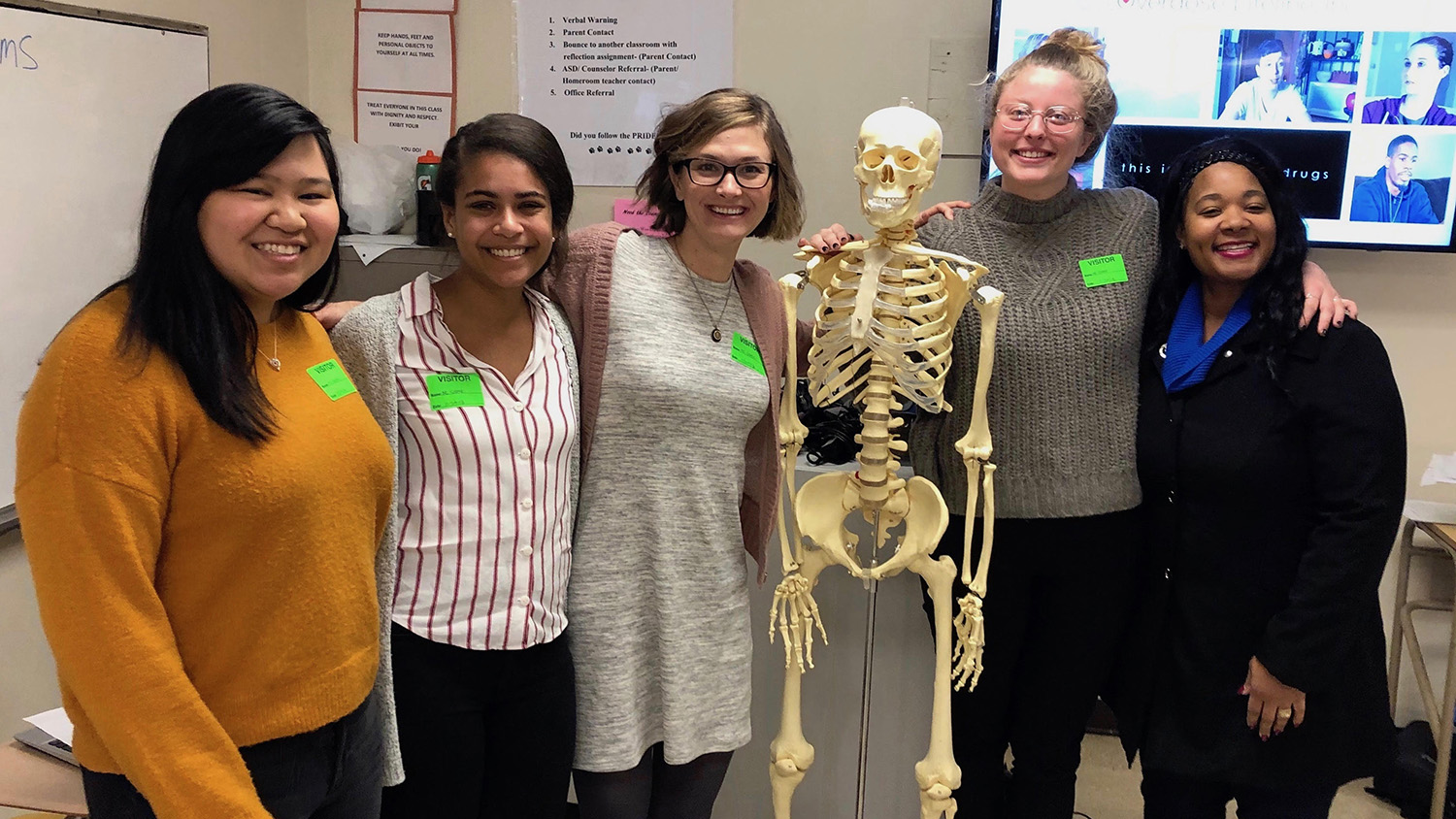 group of students stand with skeleton