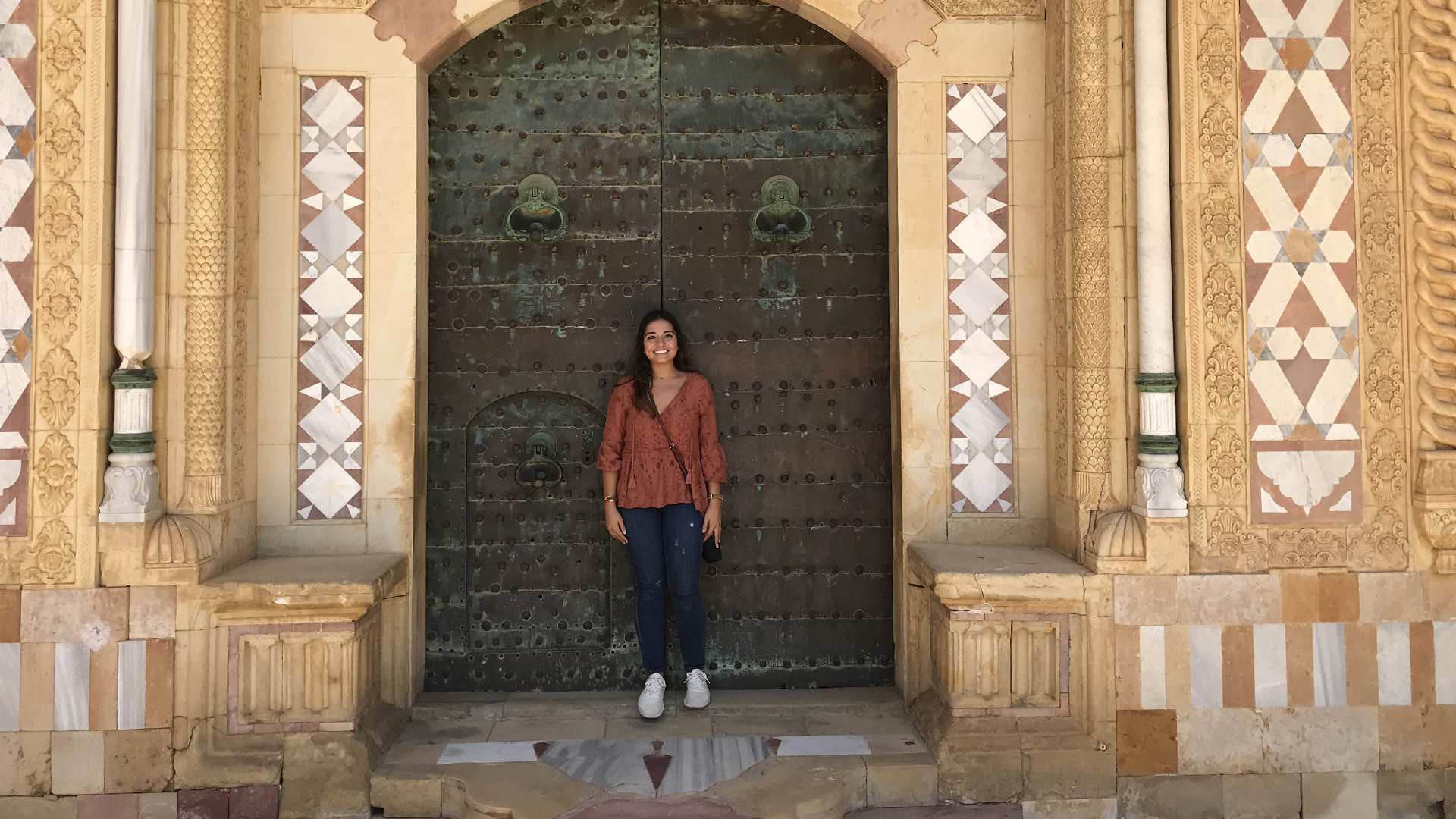 Hannah Chaya stands in front of an elaborate doorway.