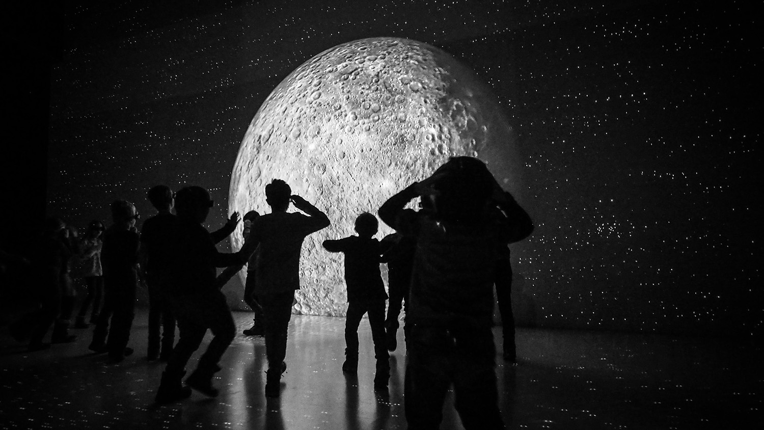students look at moon in museum