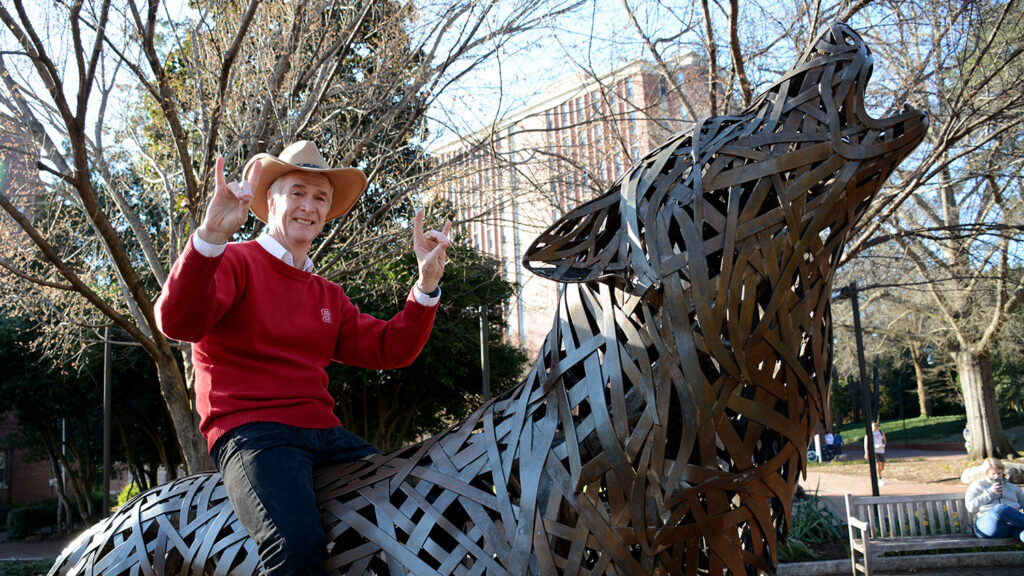 Dean Jeff Braden sits atop a wolf statue on NCState's campus