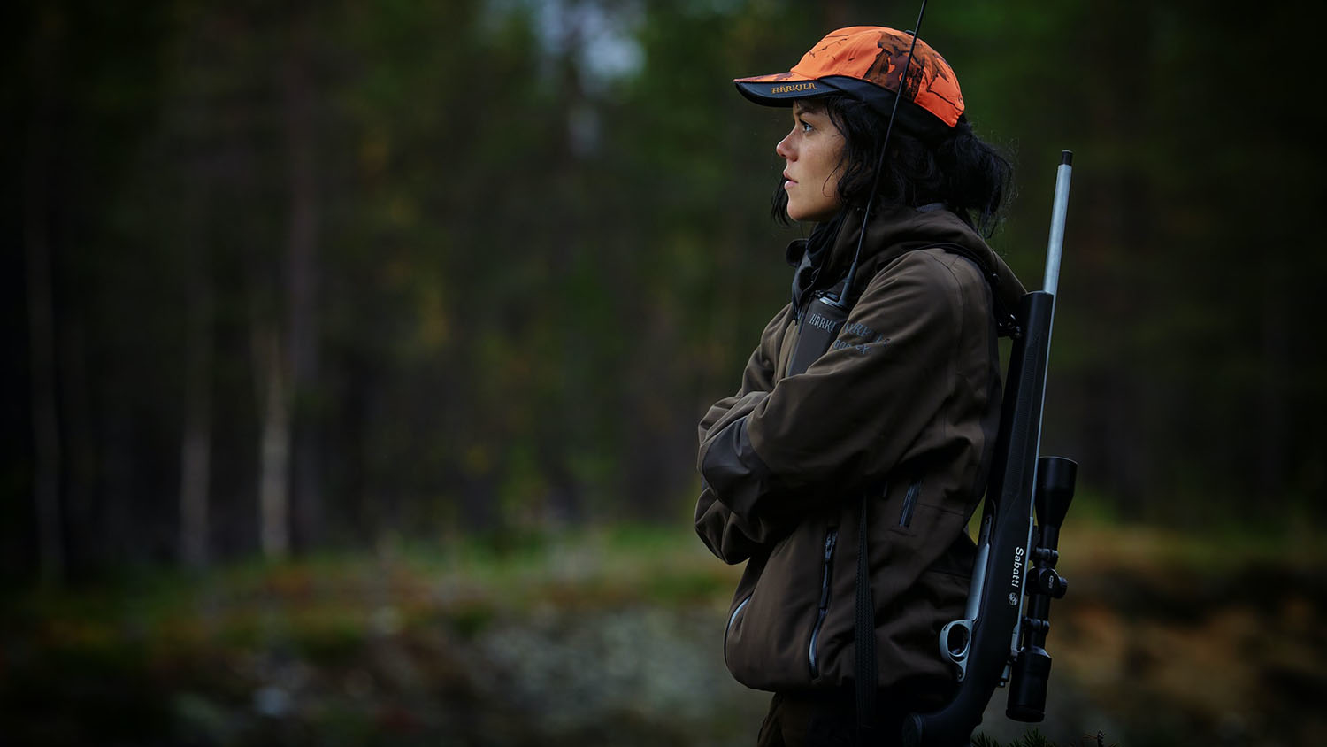 woman in hunting attire stands with rifle