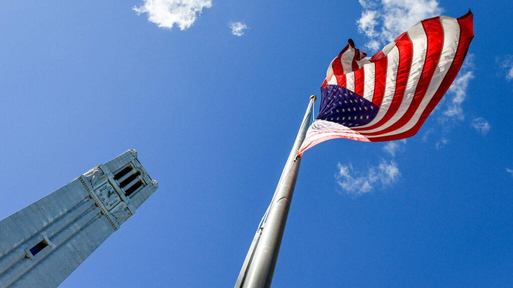 The American flag flies next to the Belltower on a sunny fall day.