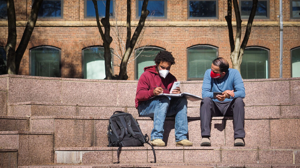 A student and a professor wear masks outside Tompkins Hall.