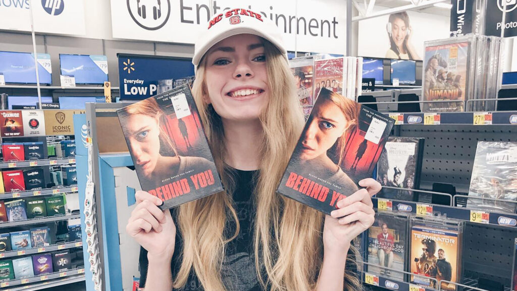 """Addy Miller holding up """"Behind You"""" DVDs"""