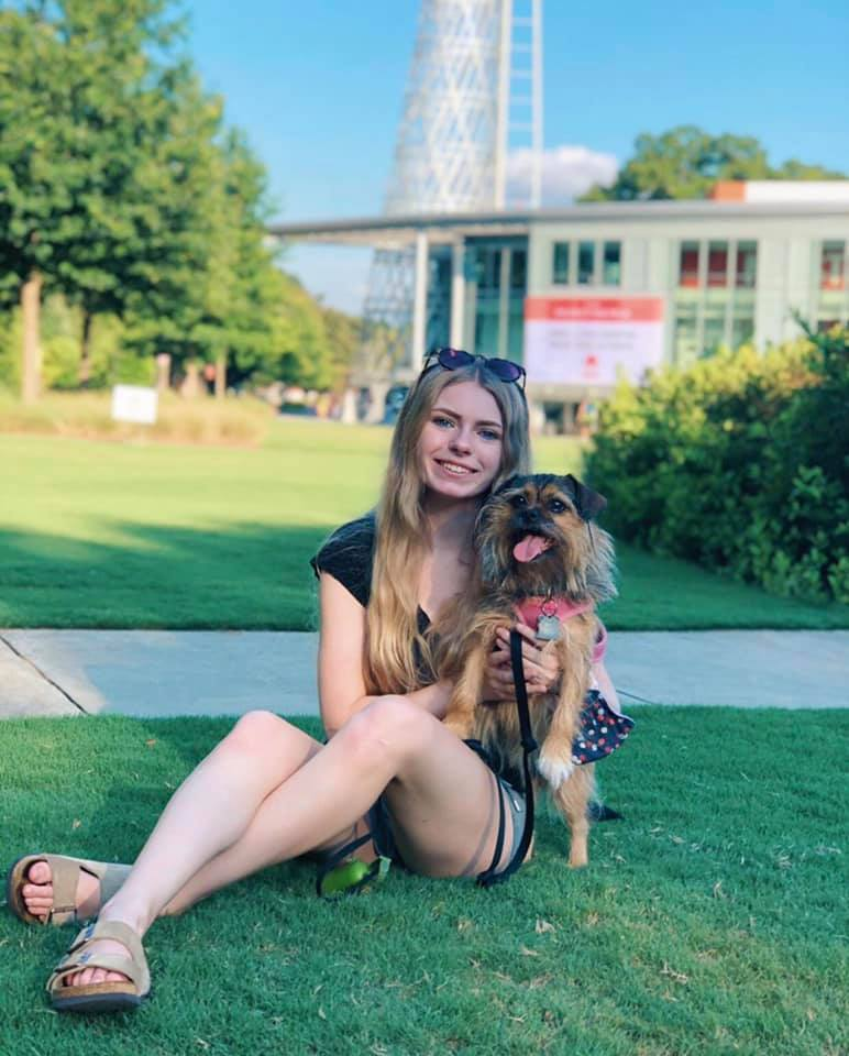 Addy Miller sitting in front of Talley Student Union with dog