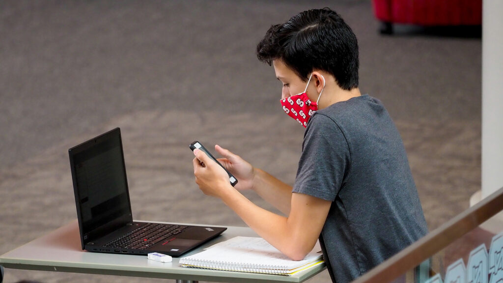 A student looks at their phone while wearing a mask