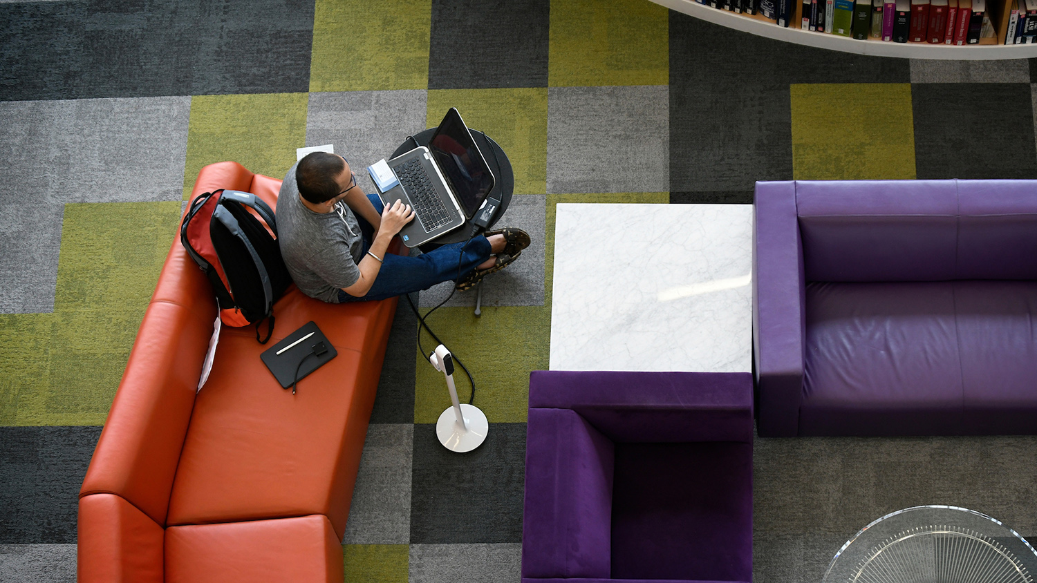 aerial view of student with laptop in library