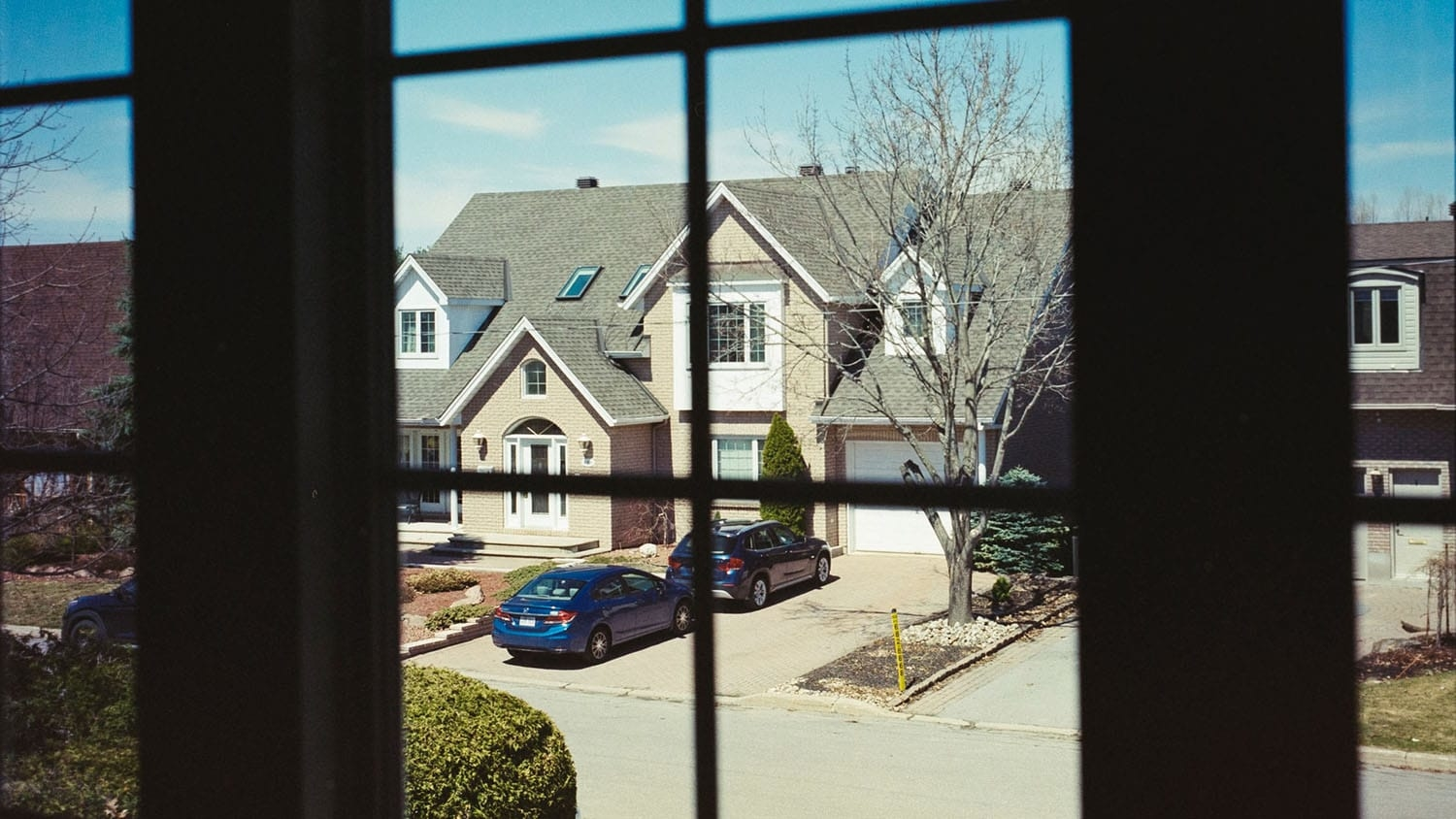 view of a suburban street from the window of one of the homes