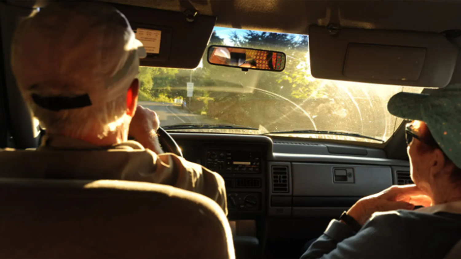older man and woman driving in car