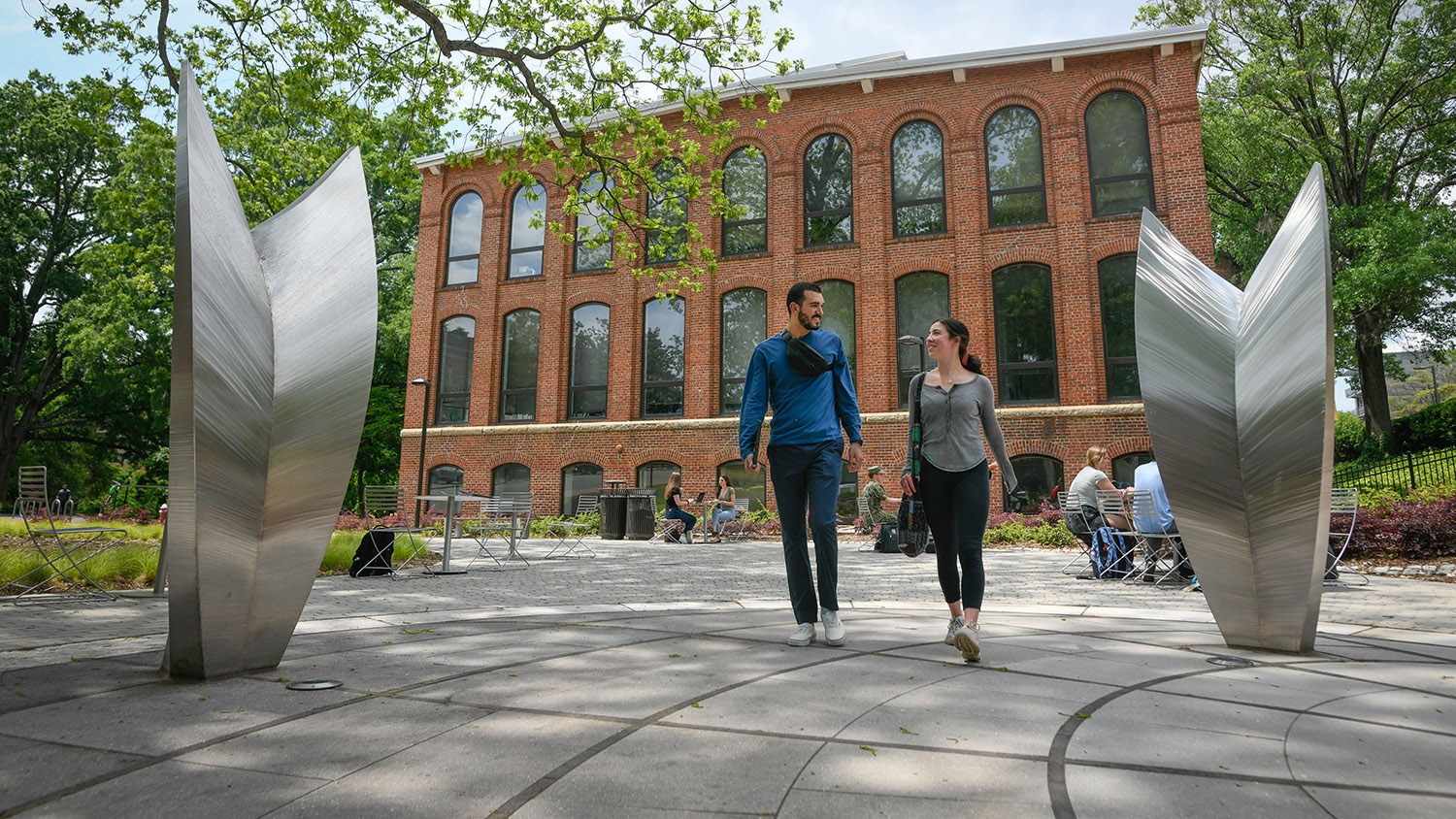 students walking in between two sculptures with brick building behind them