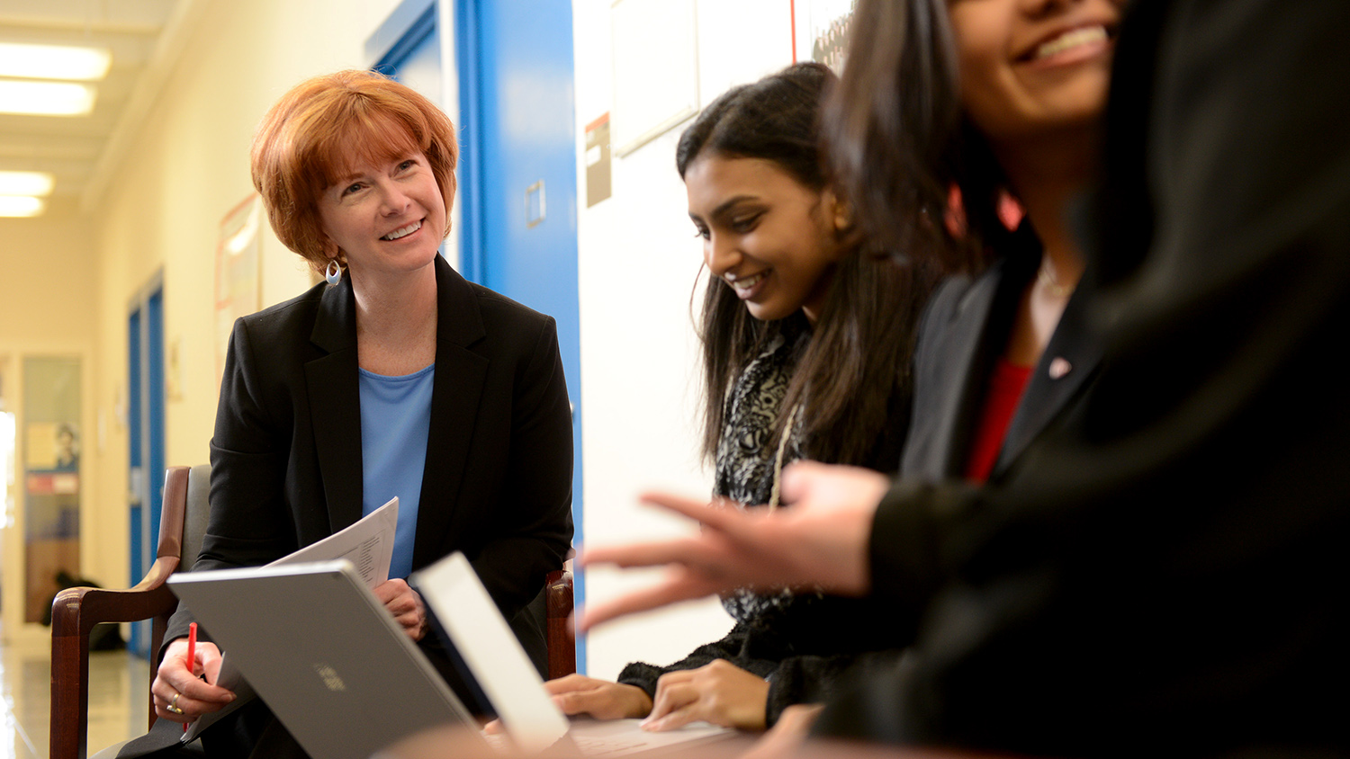 A faculty member chats with students