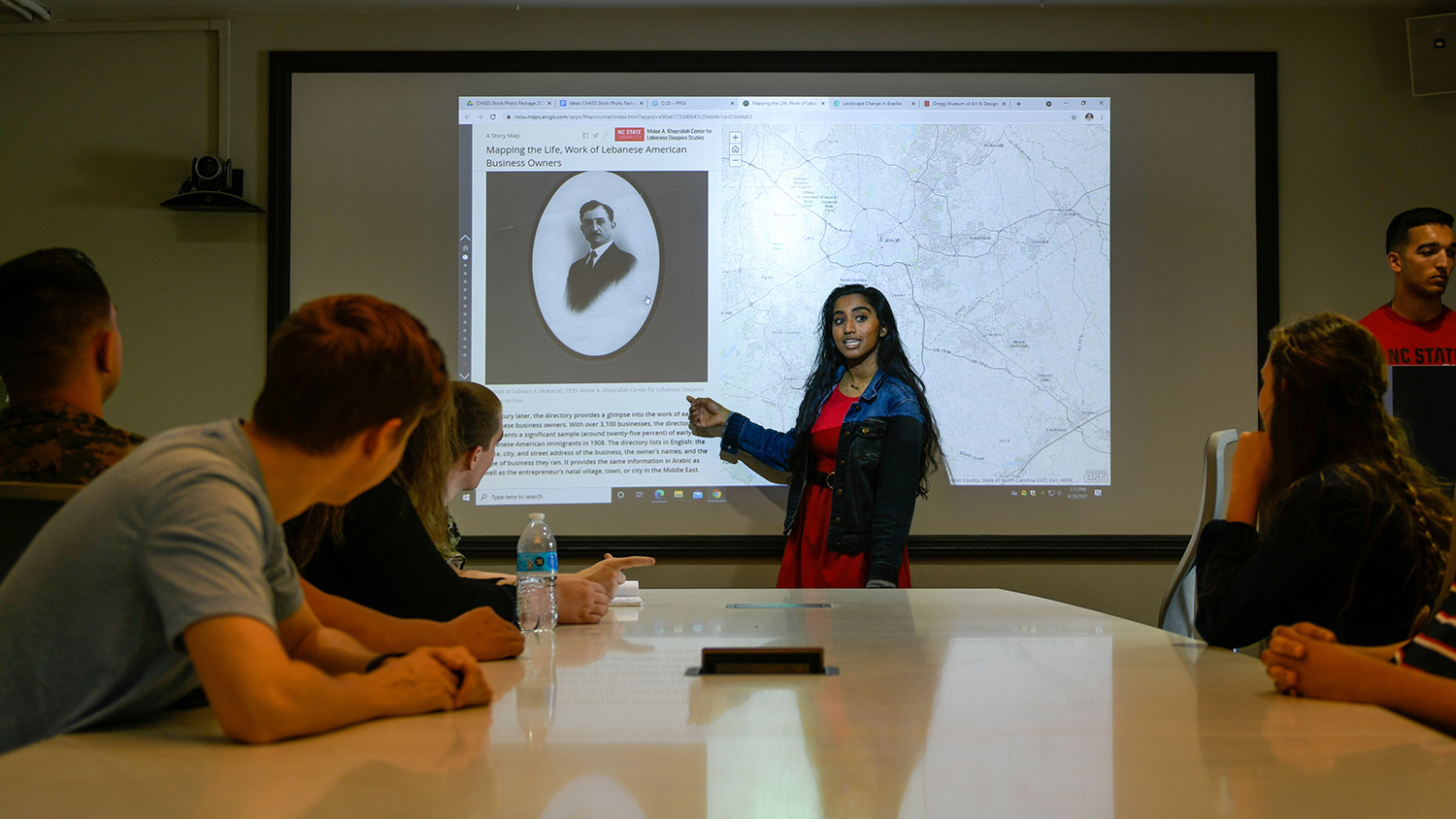 A student gives a presentation inside a conference room