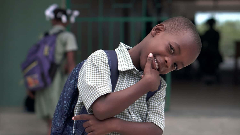 black child in a school uniform smiles at the camera