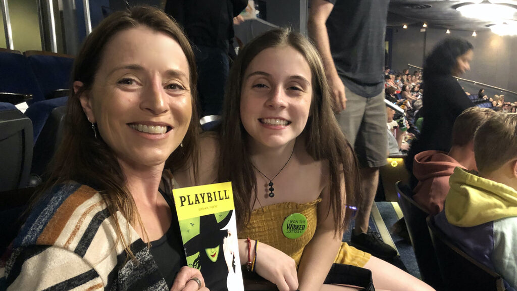 """Deanna Dannels holds up """"Wicked"""" booklet while sitting with daughter"""