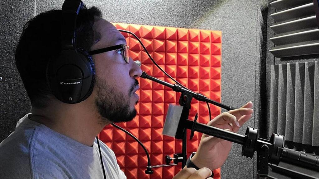 Donovan Corneetz wears a headset while speaking into microphone