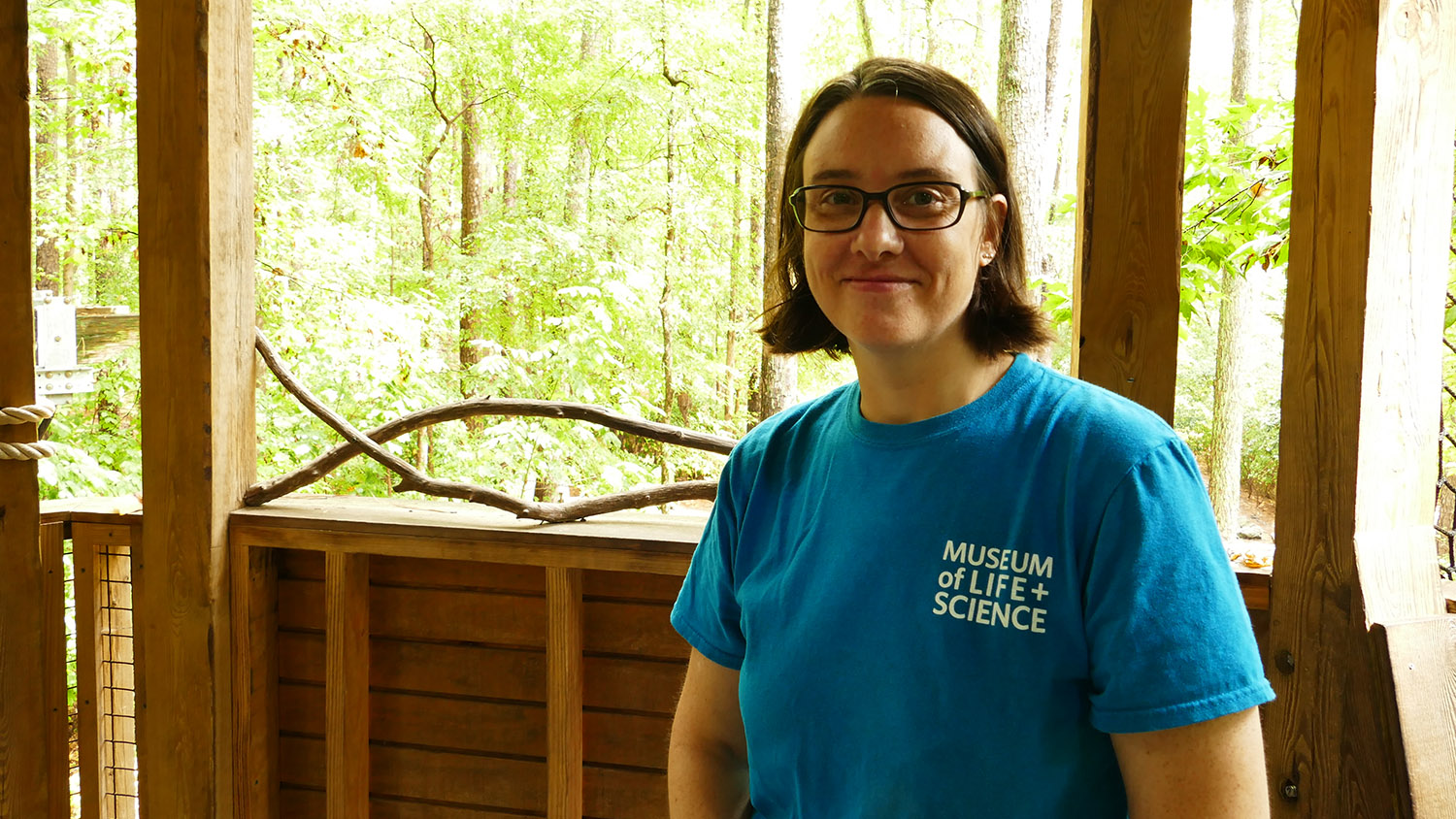 Jill Brown stands in front of exhibit wearing turquoise shirt