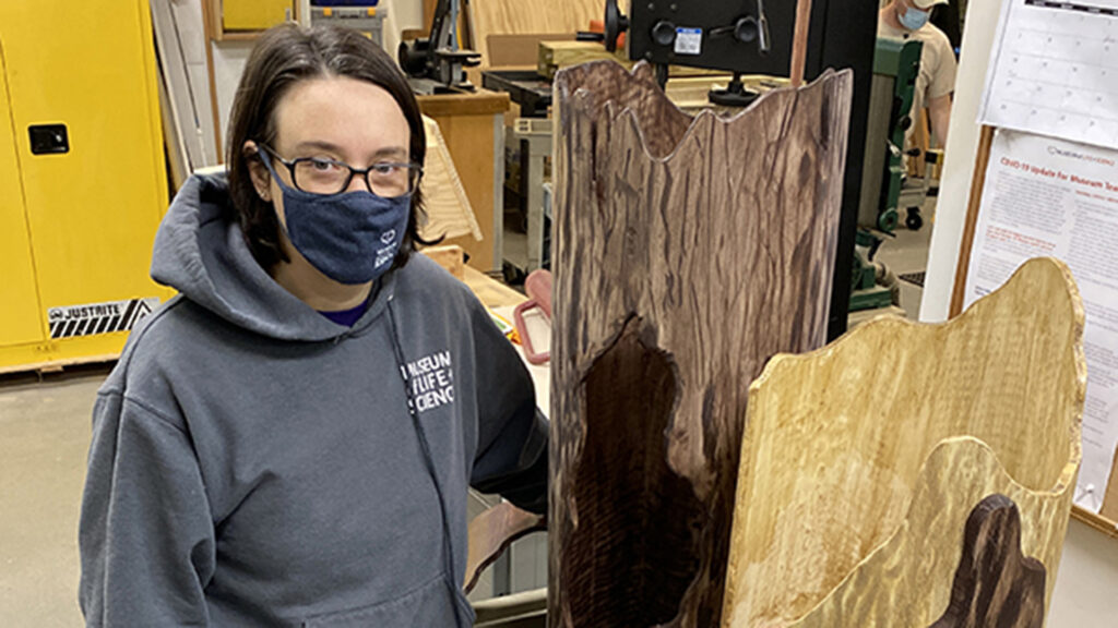 Jill Brown stands next to sleeping logs designed by her team
