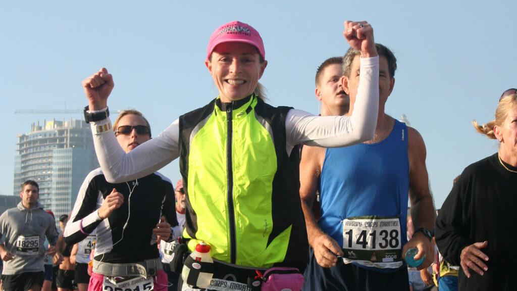 woman wearing yellow vest running in marathon